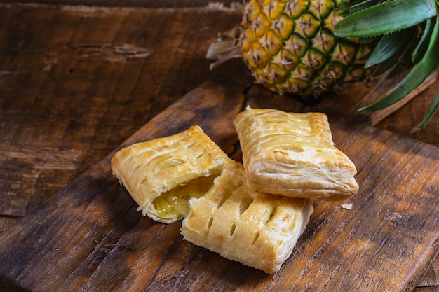 Ananastorte und ananas-frucht auf einem hölzernen hintergrund