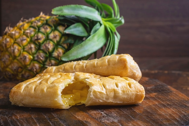 Ananastorte und ananas-frucht auf einem holz