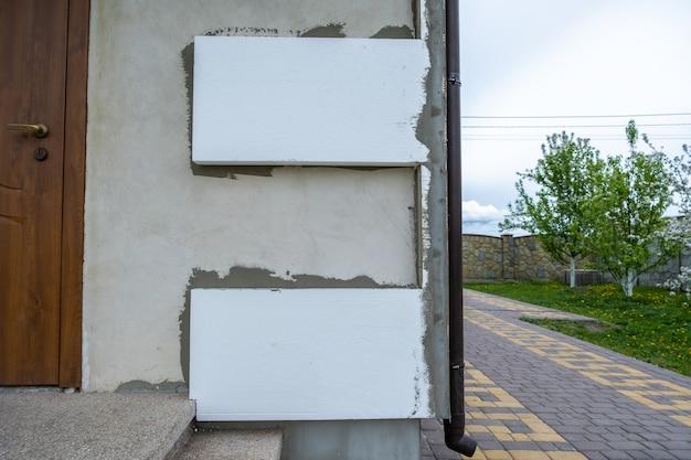 Anbringen von styropor-dämmplatten an der hausfassadenwand zum wärmeschutz.