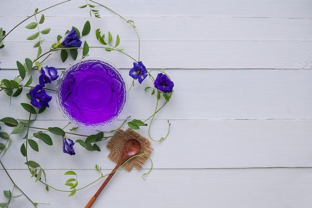 Anchan blumensaft oder blauer erbsenblüten kräutertee, schmetterlingserbse in glasschale mit holzlöffel.