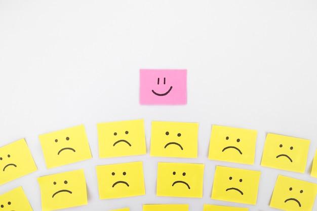 Anderes konzept. gefühle des glücks und der traurigkeit, die sich mit lächelndem sechseck von der masse abheben