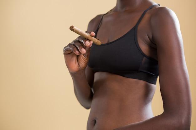 Androgyne person, die zigarre gegen beige wand hält