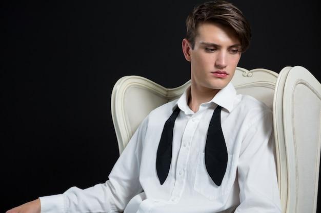 Androgyner mann, der auf stuhl gegen schwarze wand sitzt