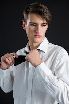 Androgyner mann, der gegen schwarze wand aufwirft