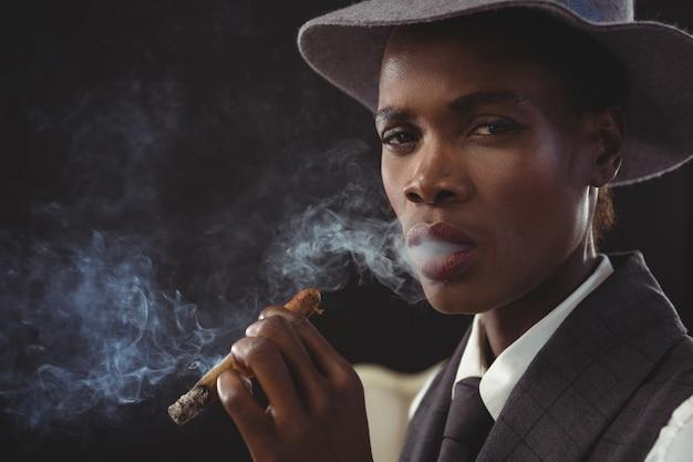 Androgyner mann, der zigarre raucht, während er auf einem stuhl sitzt