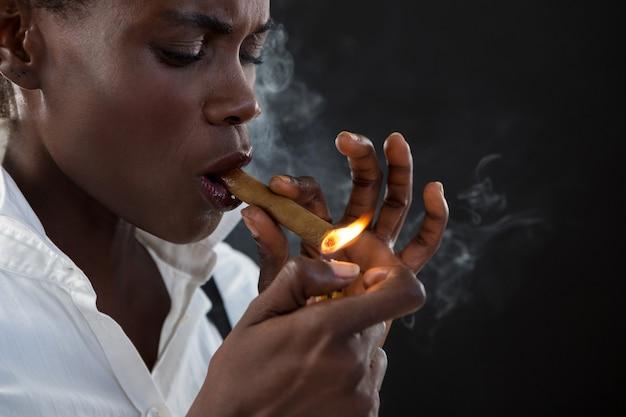 Androgyner mann zündet sich eine zigarre an