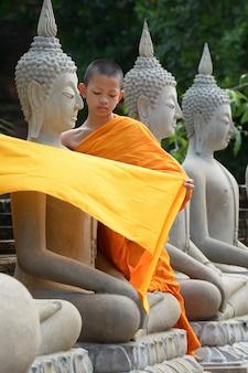 Anfänger, der das gewand der buddha-statue bedeckt, im wat yai chaimongkol, ayutthaya, thailand, 21. mai 2021.