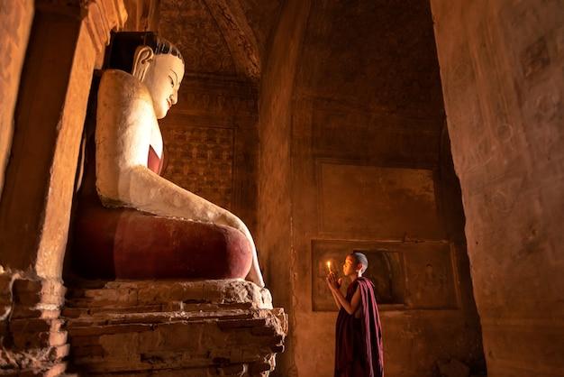 Anfängermönch, der mit kerzen vor buddha-statue innerhalb der alten pagode, bagan myanmar betet