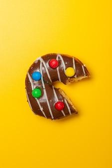 Angebissener schokoladen-vanille-donut mit süßigkeiten