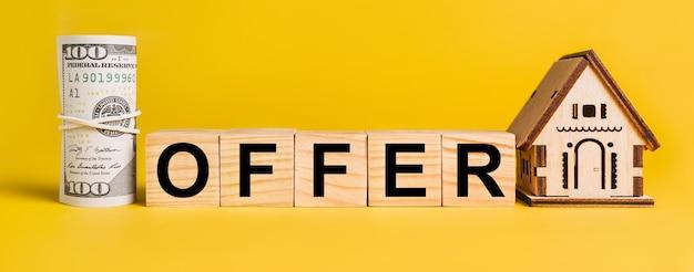 Angebot mit hausminiaturmodell und geld auf einem gelben platz