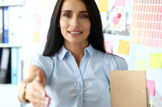 Angebotarm des schönen lächelnden weiblichen sekretärs zum kunden