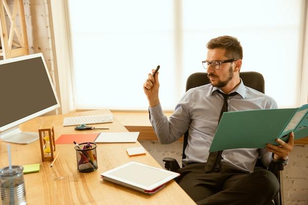 Angebote. ein junger geschäftsmann, der im büro arbeitet und einen neuen arbeitsplatz bekommt. junger männlicher büroangestellter beim verwalten nach der beförderung