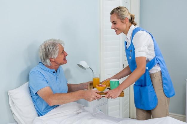 Angebotfrühstück der krankenschwester zum älteren mann, der auf bett sich entspannt