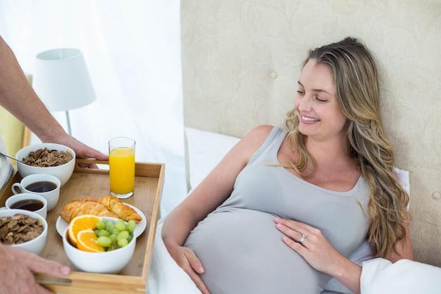 Angebotfrühstück des mannes zur schwangeren frau im bett