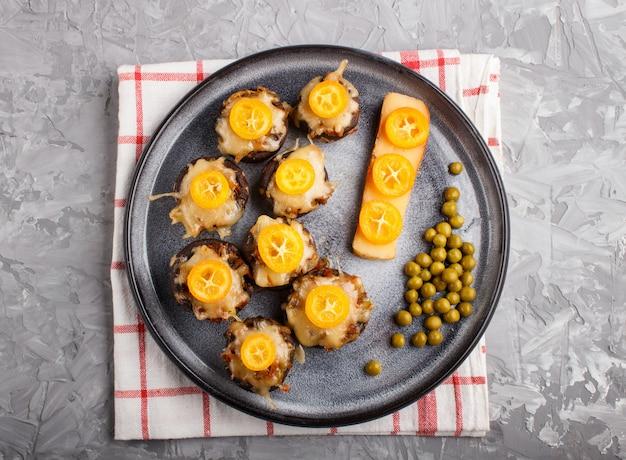 Angefüllte gebratene champignons mit käse, japanischen orangen und grünen erbsen auf grau