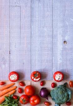 Angefüllte tomaten mit käse und unterschiedlichem gemüse auf einem hölzernen hintergrund