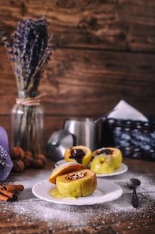 Angefüllter bratapfel mit nüssen, honig und schokolade auf weißen nachtischtellern, dunkler hölzerner hintergrund. weihnachten süß. gesundes essenkonzept.