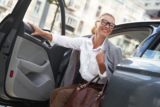 Angekommen bei der arbeit glückliche geschäftsfrau in klassischer kleidung, die aus ihrem modernen auto aussteigt und lächelt