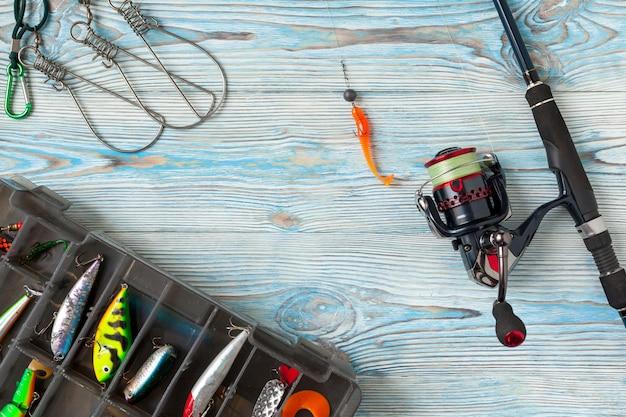 Angelausrüstung - fischen, spinnen, haken und köder auf blauem hölzernem hintergrund
