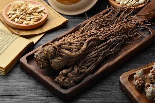 Angelica, alte chinesische medizinbücher und kräuter auf dem tisch.