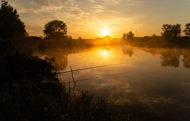 Angeln am nebligen see am frühen morgen kurz nach goldenem sonnenaufgang.