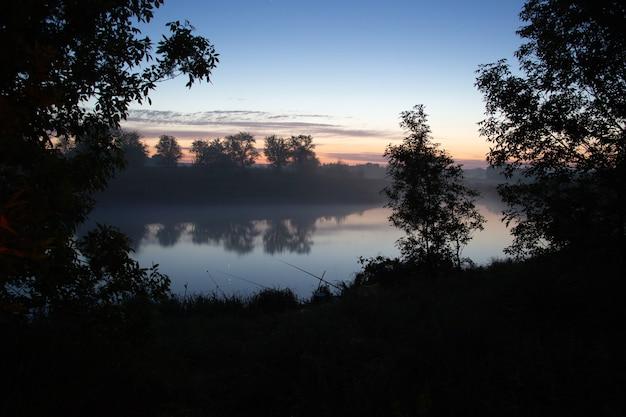 Angeln am nebligen see am frühen morgen kurz vor sonnenaufgang.