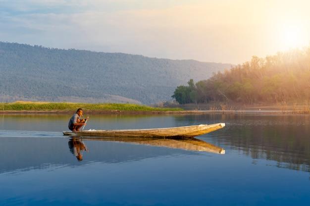 Angeln des alten mannes, der den thailändischen mann des hölzernen bootes sitzt, der ein boot auf see schaufelt