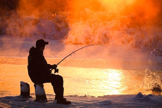 Angeln im winter auf nicht zugefrorenem stausee