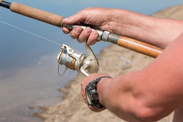 Angeln mit einem spinning auf dem fluss man fängt fische in nahaufnahme einer hand und der spinnrolle