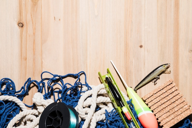 Angelrolle; fischköder; fischenfloss; kork und fischernetz auf dem tisch