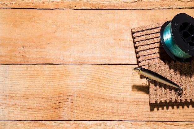 Angelrolle und köder auf corkboard auf hölzernem schreibtisch