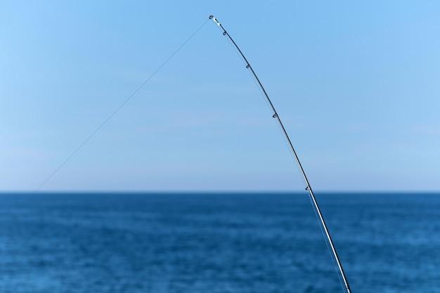 Angelrute gegen blauen ozean- oder seehintergrund