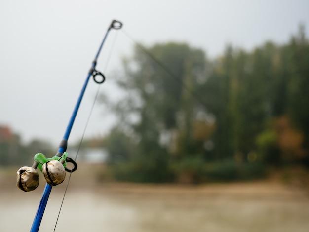 Angelrute mit glocken, um auf den biss im nebel am fluss aufmerksam zu machen
