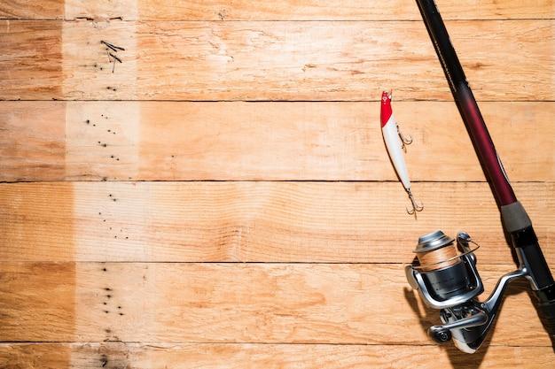 Angelrute mit rotem und weißem fischereiköder auf hölzerner planke