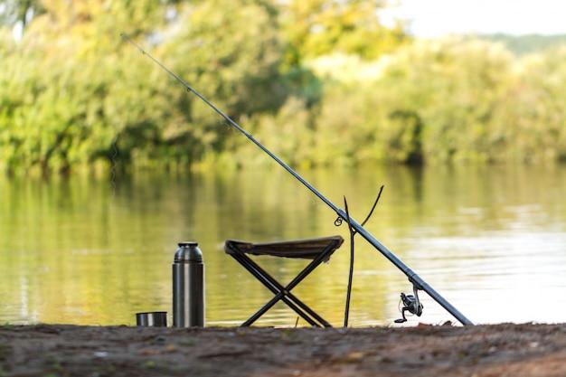 Angelrute, thermoskanne, angelstuhl auf dem hintergrund des sees. angeln.
