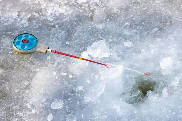 Angelrute zum winterfischen liegt auf eis