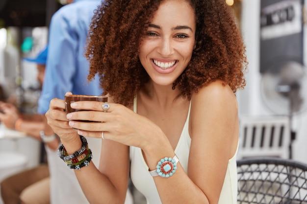Angenehm aussehende afroamerikanische frau mit breitem lächeln hält tasse kaffee oder tee, genießt pause nach hartem arbeitstag