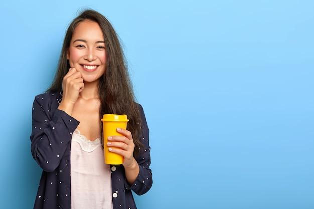 Angenehm aussehende brünette junge frau mit östlichem aussehen, berührt die wange und lächelt glücklich, trägt nachthemd und schlafkostüm, hält gelbe tasse kaffee zum mitnehmen
