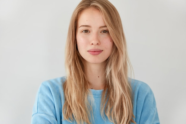 Angenehm aussehende ernsthafte blonde frau mit langen haaren, trägt blauen freizeitpullover