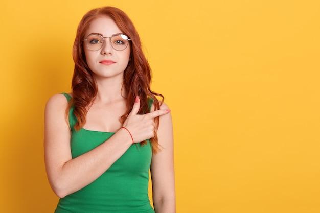Angenehm aussehende frau in brillen zeigt mit dem zeigefinger im freien raum, modelle vor gelbem hintergrund, gekleidete grüne kleidung, europäische junge frau zeigt etwas beiseite.