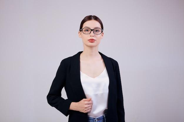 Angenehm aussehende geschäftsfrau steht auf grau in einer schwarzen jacke, einem weißen t-shirt und einer computerbrille.