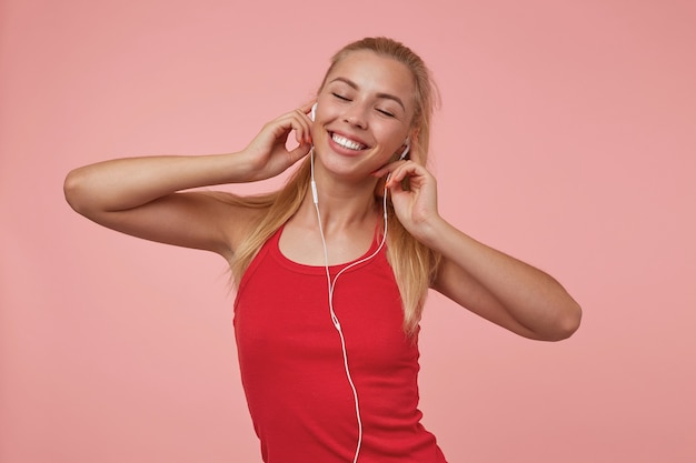 Angenehm aussehende junge blonde dame posiert mit geschlossenen augen, trägt kopfhörer und freizeitkleidung und genießt musiktitel