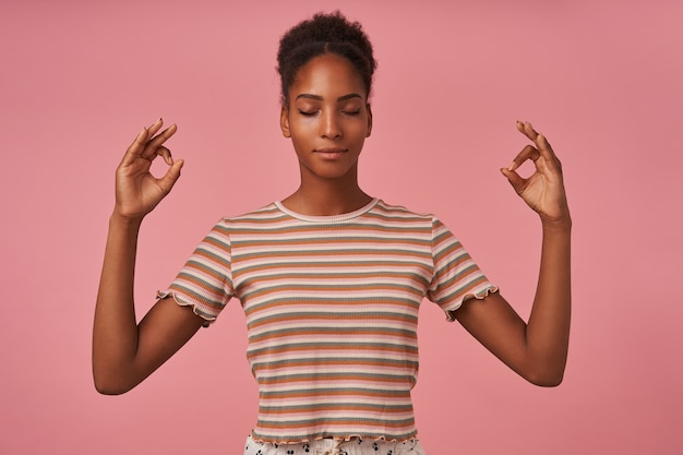 Angenehm aussehende junge braunhaarige curlyned dame, die hände mit mudra-geste anhebt, während sie mit geschlossenen augen meditiert, isoliert über rosa wand