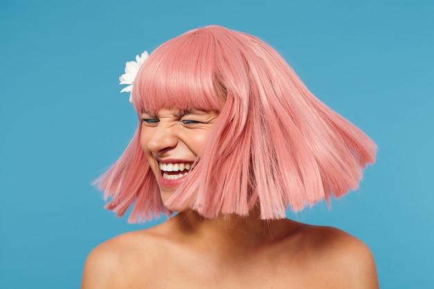Angenehm aussehende junge reizende dame mit kurzem rosa haarschnitt, der ihren kopf winkt, während er über blauem hintergrund aufwirft, glücklich mit geschlossenen augen lacht, weiße blume in ihren haaren hat