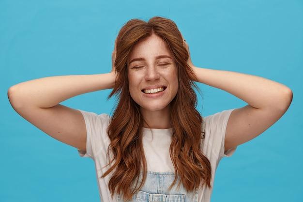 Angenehm aussehende junge reizende rothaarige frau, die ihren kopf mit erhobenen händen hält und fröhlich mit geschlossenen augen lächelt und über blauem hintergrund in freizeitkleidung steht