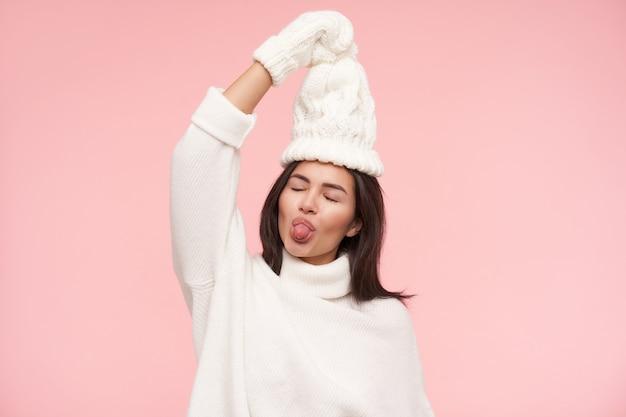 Angenehm aussehende junge schöne, die ihre zunge mit geschlossenen augen herausstreckt, während sie spaß hat, erhobene hand über ihrem kopf hält, während sie über rosa wand steht
