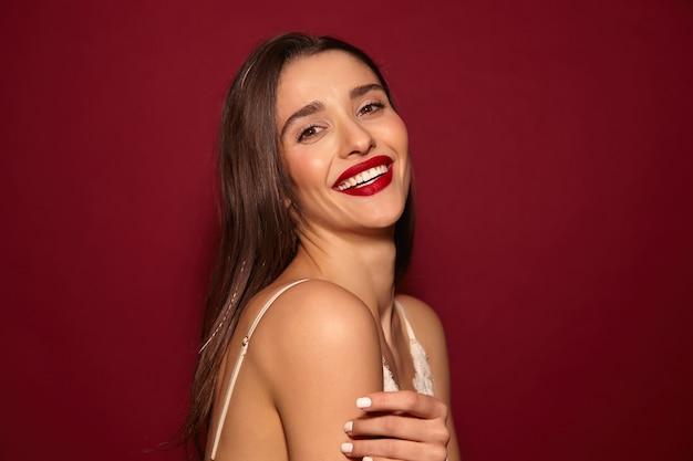 Angenehm aussehende junge ziemlich froh langhaarige brünette dame mit roten lippen