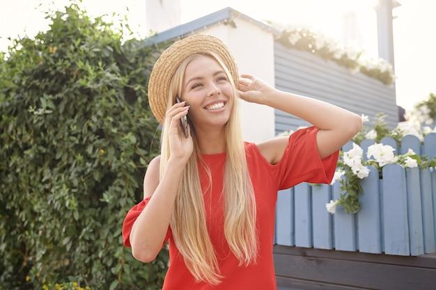 Angenehm aussehende junge, ziemlich langhaarige frau, die die hand an ihren bootshut hebt und breit lächelt, während sie ein schönes telefongespräch führt und über dem hinterhof steht