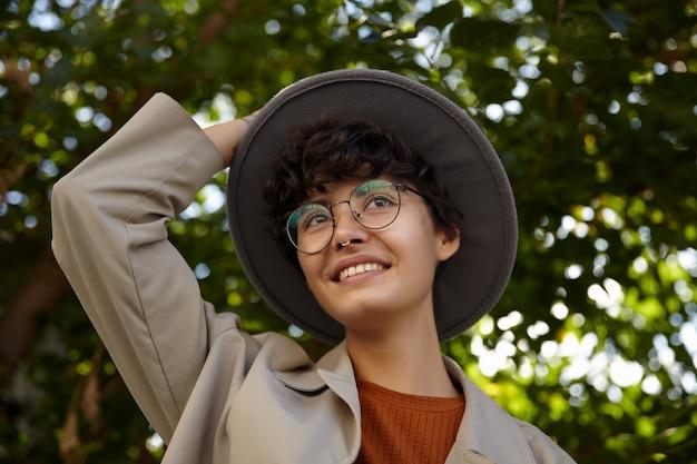 Angenehm aussehende lächelnde junge lockige frau mit kurzem haarschnitt hält ihren breiten grauen hut, während sie über grünen bäumen steht, stilvolle kleidung und brille trägt und nasenpiercing hat