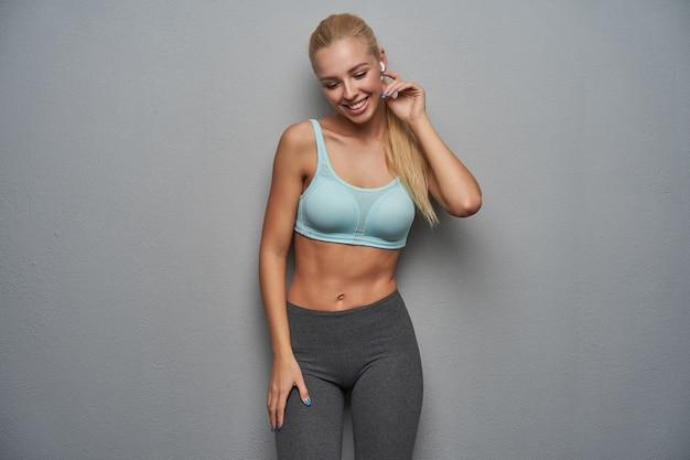 Angenehm aussehende positiv lächelnde junge schlanke blonde frau, die ohrhörer herausnimmt, während sie über grauem hintergrund steht, in guter stimmung ist und sportliche kleidung trägt